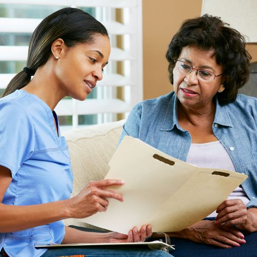 Nurse Discussing Records With Senior Female Patient During Home Visit Sitting On Sofa